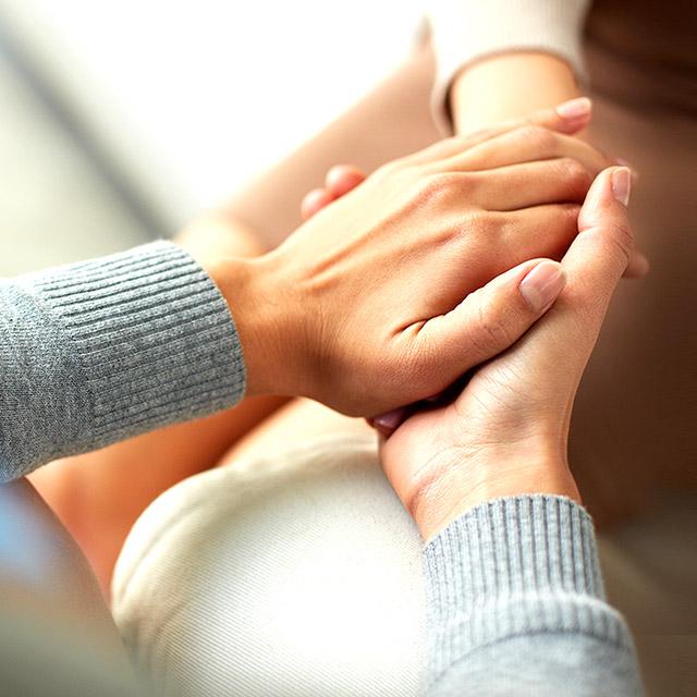 Pessoa acolhendo as mãos de outra