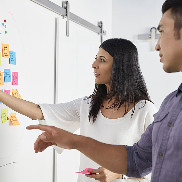 Two workers collaborating on a whiteboard covered with Post-its.