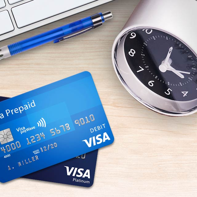 A clock, pen, and a Visa Contactless Prepaid card on a desk.